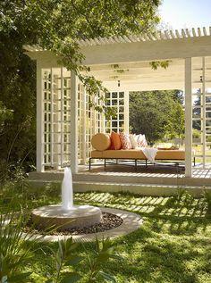 Белая деревянная беседка с перголой в саду загородного дома