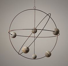 orbital mobile metal, wooden balls, room for neon or pastel. could be light fixture enliven the air above a bed or crib with their sense of movement and space.