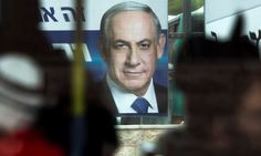 Israelis pass a campaign billboard showing Benjamin Netanyahu, prime minister and leader of the Likud party, in Jerusalem.