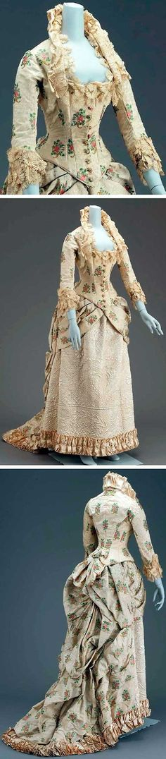 Dress in two parts, American, ca. 1880-1885. Silk & alpaca woven together. Cream background with clovers, roses, thistles in twisted horn brocaded with brilliant polychrome silks. Long-waisted bodice with center front point, slight peplum with superimposed self bow in center back. Neck trimmed with silk machine-made lace, wired pleated standing collar, under lace, of white satin. Skirt longer in back forming train. Museum of Fine Arts Boston