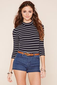 A knit top featuring an allover striped pattern, high neckline, and long sleeves.