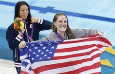United States' gold medalist Missy Franklin holds a national flag at a medal ceremony with Japan's silver medalist Aya Terakawa after the women's 200-meter freestyle swimming semifinal at the Aquatics Centre in the Olympic Park during the 2012 Summer Olympics in London, Monday, July 30, 2012. (AP Photo/Daniel Ochoa De Olza)
