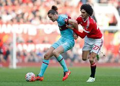 Andy Carroll in action with Marouane Fellaini