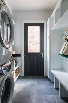 A black door fitted with a single glass panel opens to a mudroom boasting slate floor tiles and a white built-in bench fixed beneath white cubbies mounted beside stacked white shaker cabinets. Modern Farmhouse Interiors, Farmhouse Style, Farmhouse Design, Luxury Interior Design, Interior Decorating, Benjamin Moore Wrought Iron, Painted Front Doors, Iron Doors, Home Staging