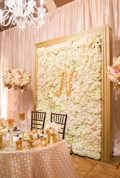 Framed Flower Wall with Monogram. An all-white flower wall with a contrasting floral monogram is a chic way to personalize your big day.