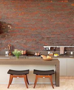 Aberta para a área externa, esta cozinha gourmet recebeu o acabamento igual ao da fachada da casa. Responsável pelo projeto, o arquiteto João Armentano cobriu as paredes com os tijolos estilo inglês. O aspecto lembra as casas londrinas