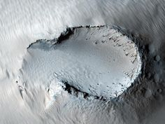 """This image is centered on a small cone on the side of one of Mars' giant shield volcanoes. The cone shows some layers of hard rock but most of it is made of relatively soft material. This appears to be an example of a """"cinder"""" cone composed of pieces of lava thrown into the air during a small volcanic eruption."""
