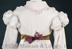 Day Coat, 1818-1820, Cotton muslin\ Cotton gauze\ Cotton piping\ Cotton pom-pom\ Cotton tape. Object ID: 2009.5.36. FIDM Museum and Galleries