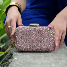 This ultra shining crystal studded clutch in pink and gold is a class apart.Pink crystals add just the right color to the clutch giving it a very classy look. Stylishly crafted it will go with every outfit of yours and add that perfect glam to the evening! Set in gold frame, it comes with detachable chain, inside pocket and matching satin lining! Go flaunt it with style! Shop now at: http://www.rusaru.com/collections/clutch-bags/products/bling-it-on-pink-clutch