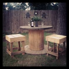 Bar table an chairs, chairs made completely of pallettes an table made from a spool.