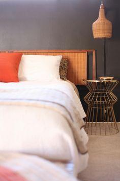 mid century danish wicker sconce cane headboard bedroom bed black wall orange brass wire table
