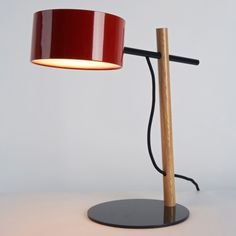 """Excel Desk Lamp  Rich, Brilliant, Willing  2010  Oak, Powder Coated Steel  Shade Finishes: White, Red  16"""" L x 11"""" w x 19"""" H  $390.00"""