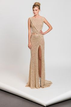 Gold lace evening gown fully embroidered with pearls, with an asymmetrical cutout waistline and a train.
