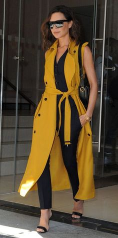 Victoria Beckham continued her (surprising) streaking of bright yellow looks, giving her sleek, tailored pinstriped separates a cheery spin with a yellow sleeveless trench (left open just so), complete with black shades and sandals.