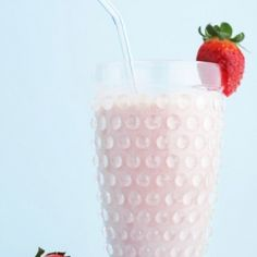 A clear glass filled with a creamy light colored pink smoothie and garnished with a strawberry on the side of the glass.