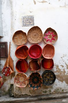 Round baskets, many colors and designs, displayed on wall