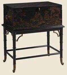 Finish: Chinoiserie.    This solid Mahogany trunk table features hand-painted Chinoiserie over a carved rattan ebony base, with gold tipping and solid brass porter's handles, corner brackets and ferrules. The inside has a rich ebony finish.