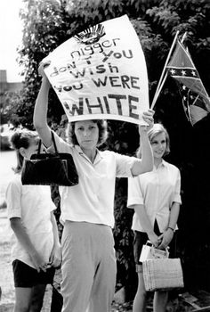 A white woman with her daughters holds Confederate flags and a sign that reads 'Nigger don't you wish you were white' to counter-protest a black civil liberties rally in Bogalusa, Louisiana, 1965.