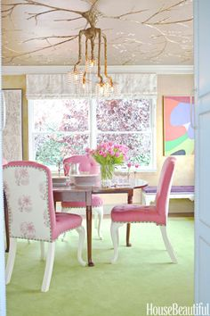 To make the Tony Duquette chandelier feel more at home, Ruthie Sommers had decorative painter Peter Bolton create an elaborate tree design in gold leaf on the dining room ceiling. Jacaranda and plum trees inspired the vibrant pink Penny Morrison fabric on the front of the chairs and the Claremont floral on the back. Rug from Melrose Carpet.