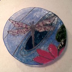 """First bowl!  Just came out of the kiln. 8"""" and shallow, I outlined the dragonfly with glass paints then used frit/frit mixtures for the coloring. I may do some detail painting, not sure!"""