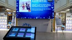Shoppers browse special offers and promotions in the centre... conveniently on a large screen.