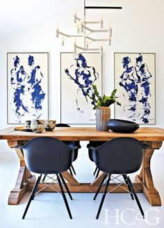 Love how the psintings on the wall complement the style of the dining table and chairs