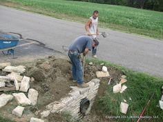 Constucting a stone culvert wall.