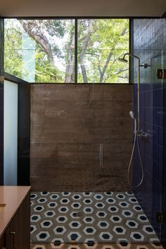 Poured-in-place concrete walls, geometric tiles and large windows make up the…