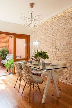 So stylish dining room with mismatched chairs and exposed brick accent wall