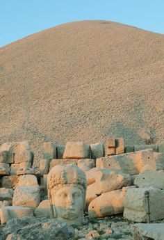 Mount Nemrut 25 miles north of Kahta, Turkey, and north of Gobekli Tepe,  is another artificially covered mountain top above large stone heads of people  and animals. The artificial mountain top rises 164 feet above the carved statues  that appear to have Greek-style facial features, but Persian clothing  and hairstyling.
