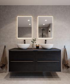 Et lunt og varmt baderom med mørke armaturer og møbler. De dempede, varme gråtonene på flisene og veggene innbyr til ro og trivsel i baderommet.  MIE baderomsmøbel i sort eik gir hele rommet et mykere og moderne uttrykk.