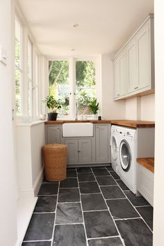 slate floors and wooden countertops in the laundry room.