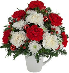 Christmas Peace Mug - A reusable coffee mug is arranged with red and white carnations, plus chrysanthemums, red berries, red ornamental balls and seasonal greenery.