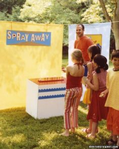 The target table: a white box decorated with blue construction-paper waves and topped with red contact paper. We covered a strip of foam board with the same paper, inserted golf tees into it, and secured it to the box with double-sided tape. Kids get one ticket for each ping-pong ball they knock off a golf tee with spray from a water gun.