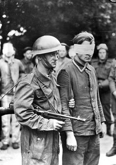 An unidentified Canadian soldier, who is armed with a Thompson machine gun, escorting a German prisoner who was captured during Operation JUBILEE, the Dieppe raid. England, 19 August 1942