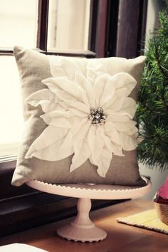 "I have fallen in love with this Christmas pillow.  ""This one is made with a khaki cotton that has a linen look that's on a 12 inch pillow form.  The poinsettia is just a bunch of petals cut out of ivory felt and stitched down with linen floss.  I used buttonhole twist thread to stitch the jingle bells,"" from mybricole."