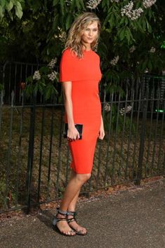 Kloss at an event in London wearing a Stella McCartney dress and gray and black lace-up flat sandals.