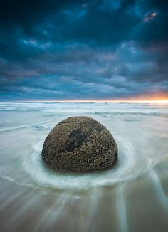 Moeraki Boulder, Otago New Zealand. Long Exposure motion blur creates a dynamic tension between the static boulder and the relentless sea. Note the other dynamic ingredients added to this image - interesting perspective, use of colour, vision-lock, foreground/background interest.  Read more: http://digital-photography-school.com/composing-dynamic-landscape-images#ixzz2aAncYeq6