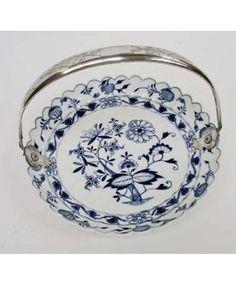 Een Zwiebelmuster porseleinen gebaksschotel, gemonteerd met een gegraveerde zilveren beugel. Het porselein gemerkt met het gekruiste zwaardenmerk van Meissen, de zilveren beugel gekeurd met het meesterteken van Cornelis Begeer, Utrecht, jaarletter 1867.Doorsnede 265 mm.