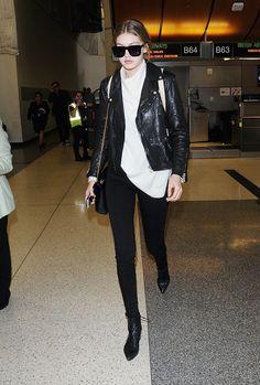 Gigi Hadid wears a chunky sweater, moto jacket, skinny jeans, and booties