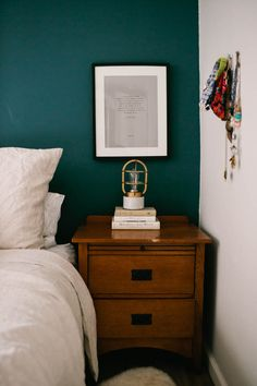 Gorgeous relaxing bedroom with a dark blue green / teal feature wall, white walls, with warm wood and gold accents