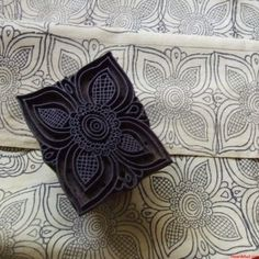 Lineoleum block printing.  Draw the desired design on a tracing paper. Use carbon paper to trace design onto linoleum wooden block and darken traced design w-permanent marker.  Carve traced design on the linoleum wooden block using the carving knives. App
