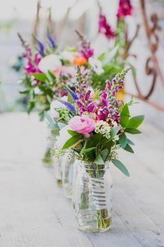 Bij de lente horen bloemen! Creëer je eigen bloemenzee op jullie lentebruiloft met heel veel bloemenvaasjes. Fotograaf: Heirloom Collective // Girls of honour