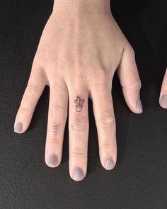 Tiny minimalist arrow and cactus tattoos on the fingers.