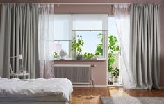Világos hálószoba, fehér rolókkal, egy réteg fehér függönnyel, ami megszűri a napfényt és egy réteg vastag szürke black-out függöny a privát szféráért.