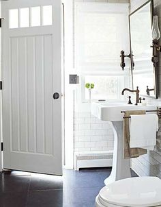 bathrooms - white pedestal sink white subway tiles backsplash white roman shade oil-rubbed bronze faucet pivot mirror sconces black stone floor