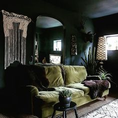 I just want to curl up on this couch. black walls and green sofa by cowboy kate