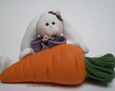 Lapin blanc en argile polymère converti une carotte dans son mode de transport. Un petit ours portant des oreilles de lapin est attraper un tour du lapin. Mesure 2 de hauteur par 3 1/8 de long  Prêt à expédier. Il sagit de la création dargile de polymère réelles que vous recevrez.  Chaque création est une œuvre dart individuel faite par moi, Helen.  Argile Art Hélène