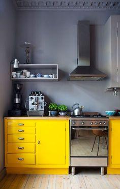 Dans cette immense cuisine, on craque pour les murs et plafonds peints dans une teinte de gris très soutenue et qui contrastent avec les meubles jaune !