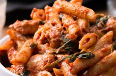 4 tablespoons olive oil  3 tablespoons salt  1 pound penne pasta  3 cloves garlic, chopped  2 chicken breasts, cubed  1 tablespoon pepper  1 28-ounce can crushed tomatoes  ½ teaspoon red chili flakes  ½ cup heavy cream  5 ounces spinach  ½ cup parmesan cheese  Garnish  Additional parmesan cheese